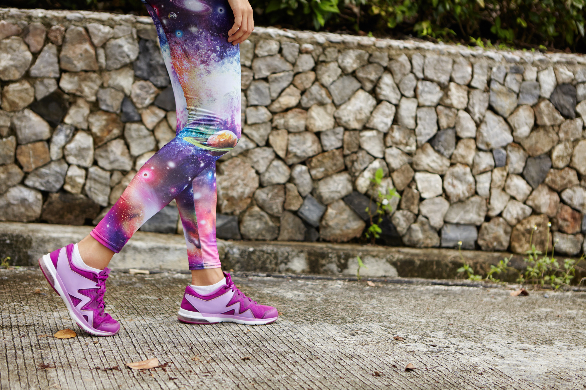 Outdoor portrait of female runner with fit athletic legs wearing purple sneakers walking along concrete path in urban park, catching her breath after intensive workout, preparing for marathon