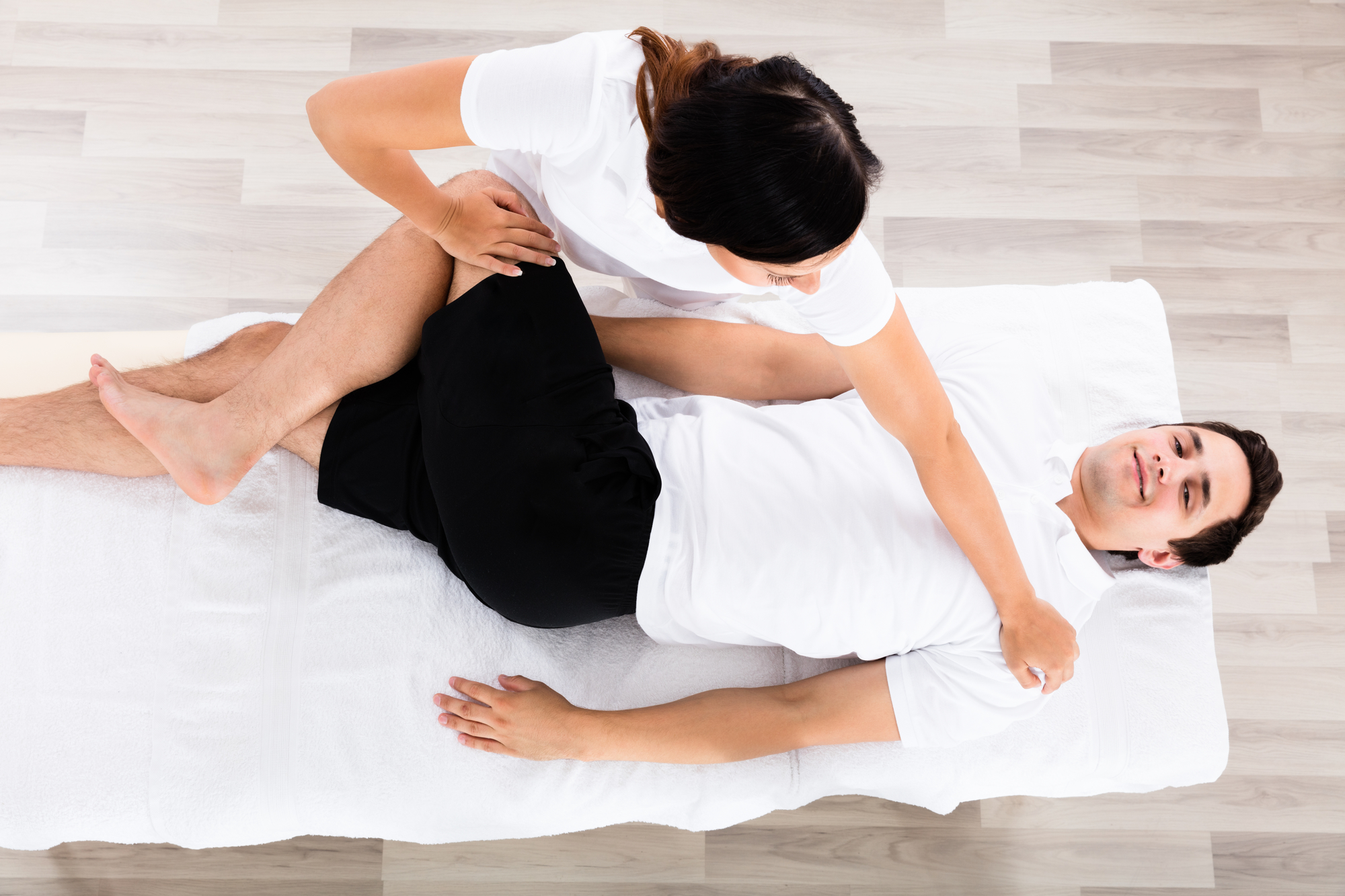 Young Female Therapist Massaging Relaxed Man's Leg