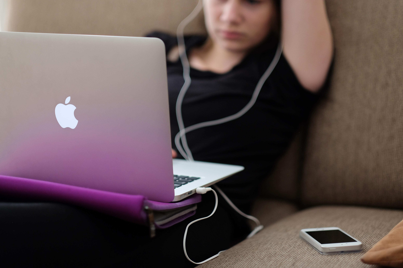Pige med hørertelefoner sidder i sofa med sin computer